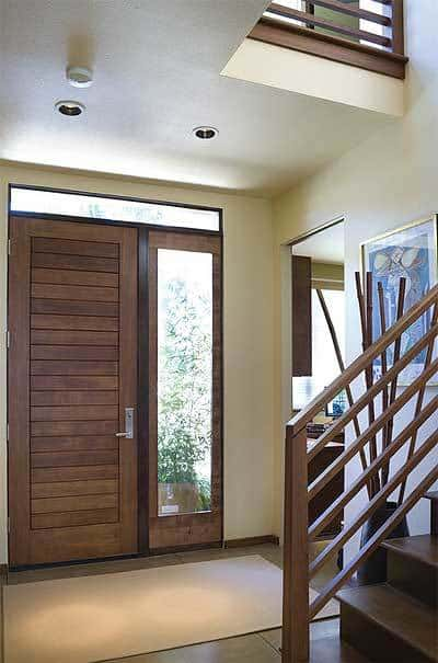 This is a close look at the simple foyer with a wooden main door complemented by the side light and transom window that also bring in natural lighting for the beige walls and ceiling.