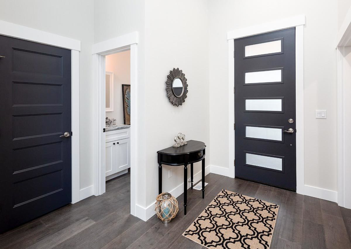 Dark wood front door and console table create a stunning contrast to this white foyer. It is adorned with a sunburst mirror and a patterned rug that lays on the hardwood flooring.