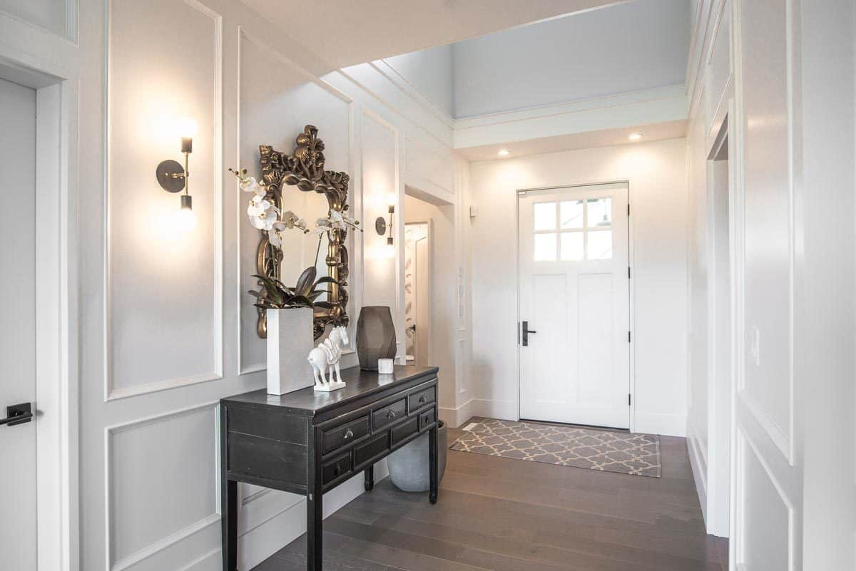 This is the foyer of the house with elegant white wainscoted walls adorned with wall-mounted lamps. These are then contrasted by the dark wooden console table and the dark hardwood flooring.