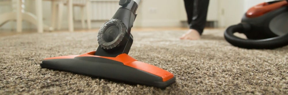 Vacuum cleaner used on a carpet flooring.