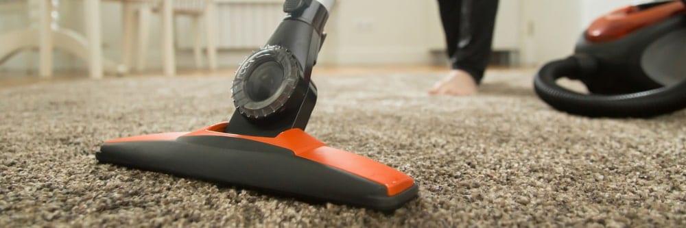 Vacuum cleaner used on a carpet flooring.