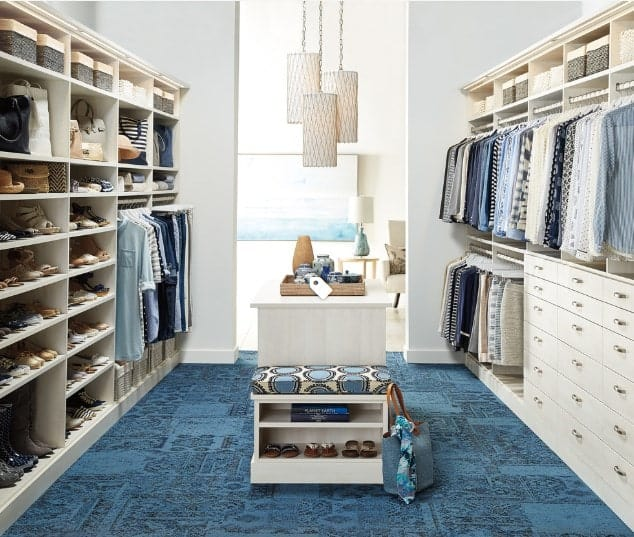 This ocean-style walk-in wardrobe features various hues of blue and pale ivory whites for an extremely captivating design. The azure blue carpeted floor pairs go well with the pastel storage shelves. The cylindrical lamps make a striking adornment too.