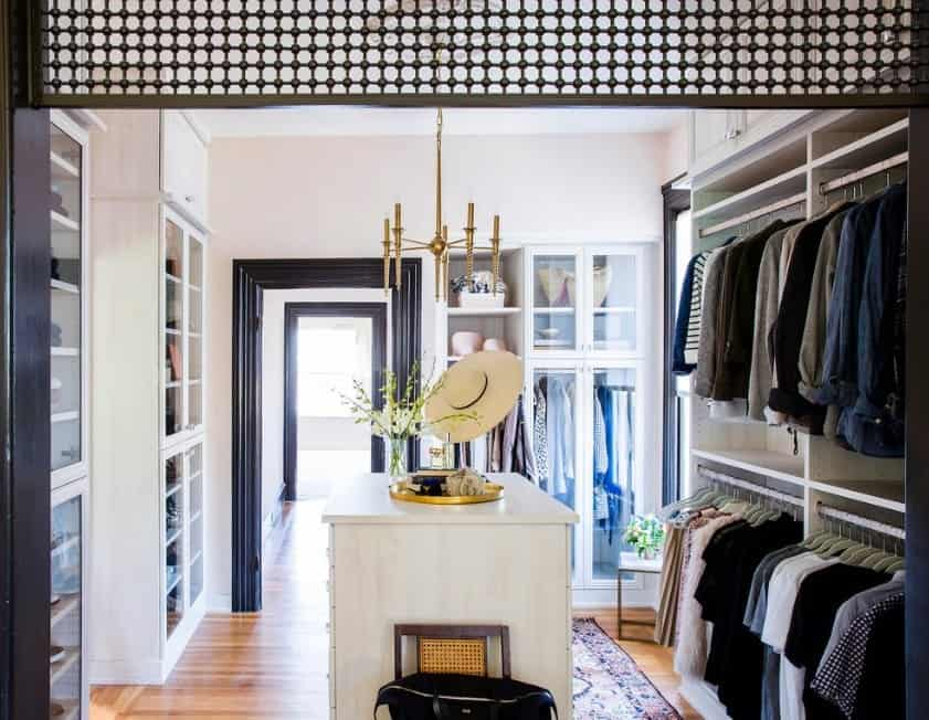 This walk-in closet demonstrated how a sleek and slender center light and some trendy accessories on the island can uplift the ambiance in a small space.