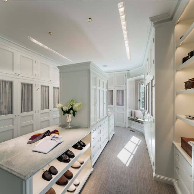 This walk-in wardrobe features an angular design that adds a fascinating twist to the room. Quite literally! Notice the light gray drapes that enable you to cover the open storage compartments if needed.