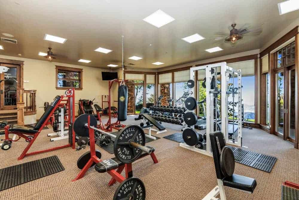 This home gym also boasts its large space, full equipment, a sandbag hanging in the middle and lovely relaxing treetop view outside the tall glass windows. Photo credit: Adrian Van Anz and Jason Speth Source: www.eaglecrestmountain.com