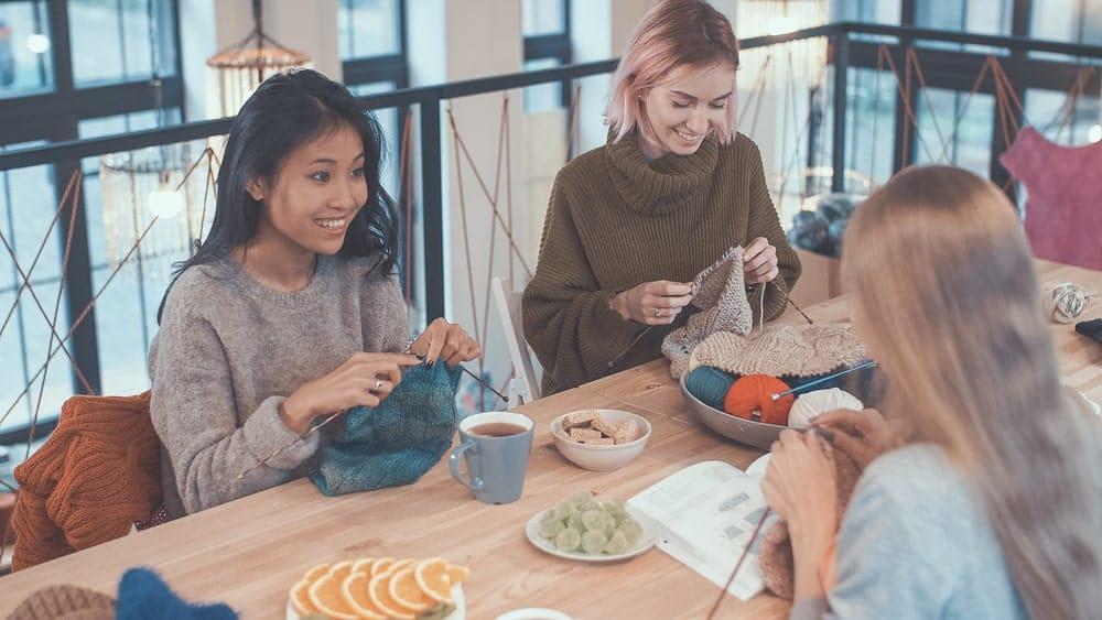 A trio of young ladies knitting over coffee and snacks.