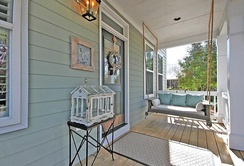 This porch looks like one from the ancient times with antique decorative pieces, a funky porch swing and wooden floors with a designed portion in front of the entrance door.