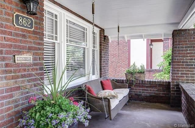 As pretty as the picture, this porch design is just gorgeous with a cute porch swing, a huge planter on the side with colored flowers and a brick theme throughout the walls.