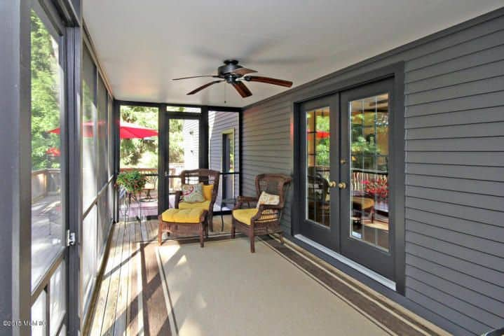 If you have a knack for experimenting, you will like this design for your porch. It uses a combination of grey walls and grey doors with brown wooden flooring and wooden furniture with brightly colored seat cushions. Unlike many porches, it is closed off from all sides and has a fan instead for ventilation purposes.