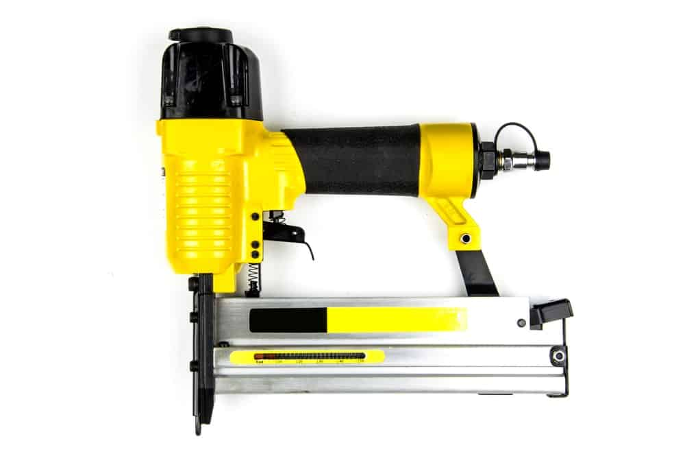 Yellow Pneumatic Staple Gun resting against a white surface