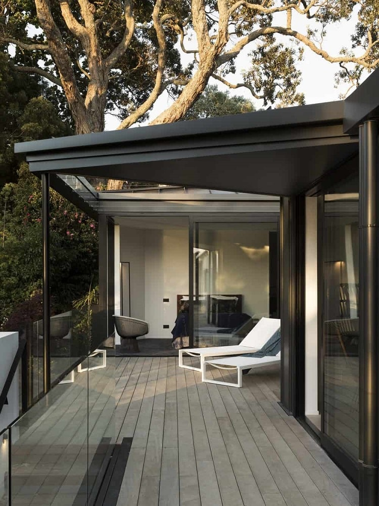 This is a wooden deck terrace with glass walls and dark metal beams to match the wooden flooring and the white lounge chairs facing the view.