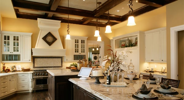 The dark wooden cabinetry of the kitchen island matches perfectly with the coffers of the ceiling that is augmented by the lovely decorative pendant lights that throw off warm yellow lights.