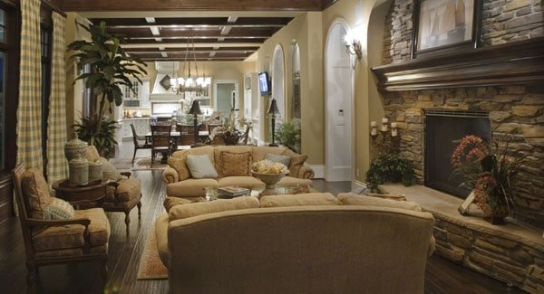 This gorgeous living room is part of a great room that also houses the dining area and kitchen. The living room area is dominated by the large stone fireplace across from the beige sofa set that complements the dark hardwood flooring.