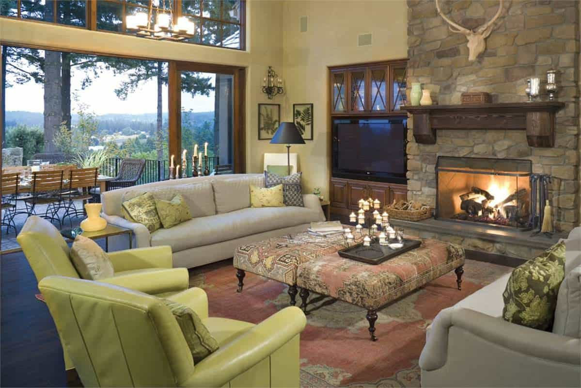 The gorgeous stone structure that houses the fireplace is topped with a floating shelf and wall-decors. Across from this is the pair of gray sofas and green cushioned arm chairs surrounding the coffee table.