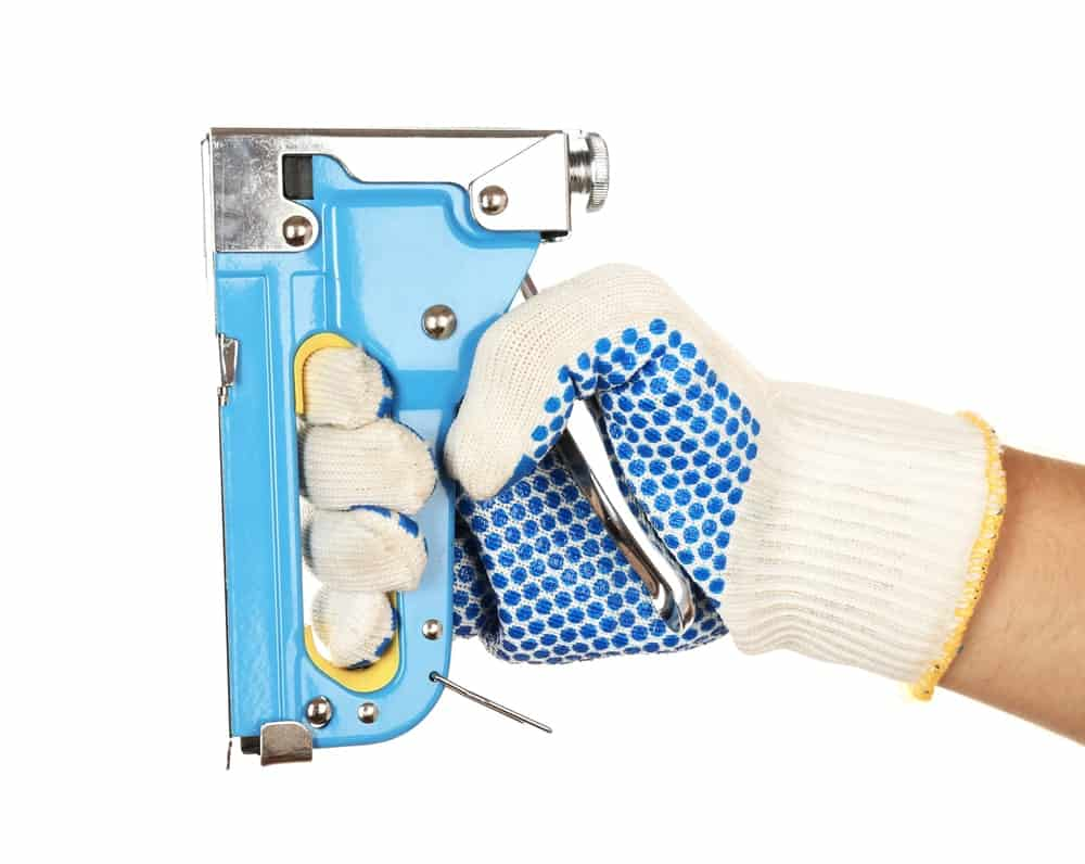 Blue Manual Staple Gun being gripped