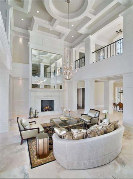 This is a grand living room with a soaring high coffered ceiling that hangs a chandelier. These are reflected by the massive wall-mounted mirror above the fireplace across from the sofa and the two arm chairs surrounding the glass-top coffee table.