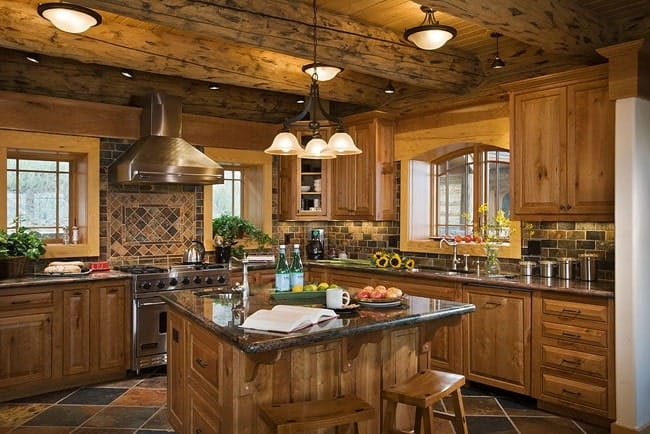 This rustic and homey kitchen has large wooden beams on its ceiling that hangs warm decorative lighting over the square wooden kitchen island that matches well with the surrounding cabinetry complemented by the earthy flooring tiles and the stainless steel appliances.