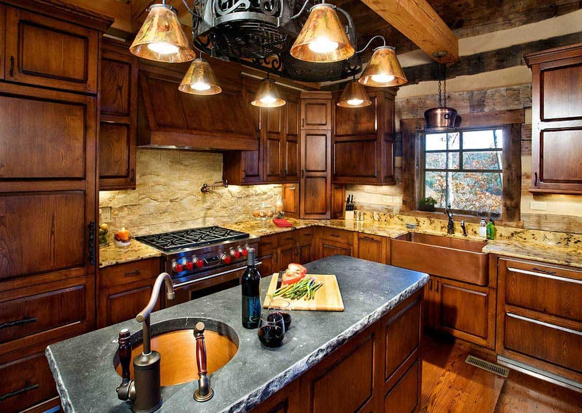 This gorgeous kitchen is complemented by the elegant dark wooden cabinetry of the walls that match with the kitchen island. This is then augmented by a rustic stone slab countertop topped with a wrought iron decorative chandelier hanging from the exposed beams of the wooden ceiling.
