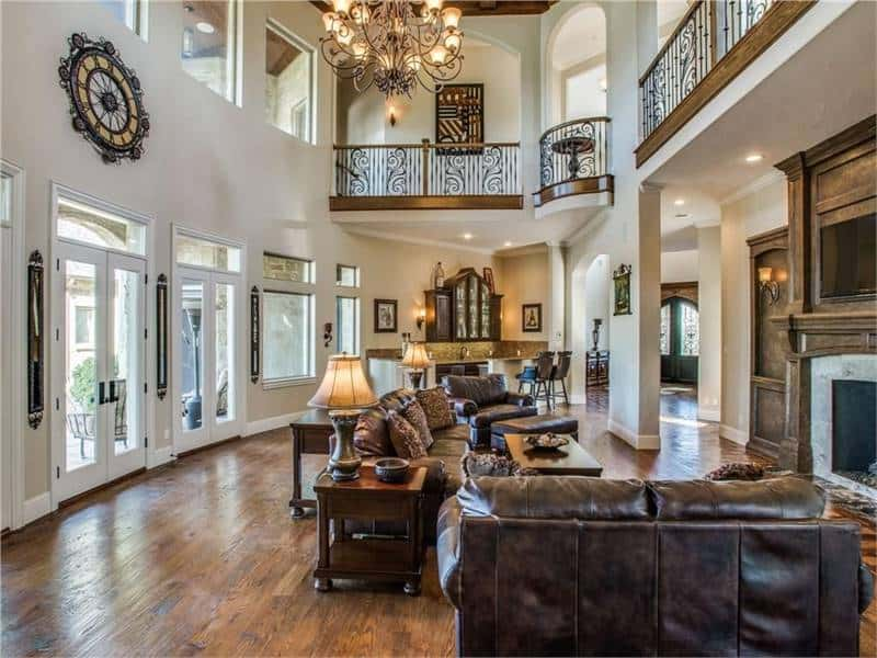 This spacious and airy living room has a dark brown leather sofa set facing a large fireplace. These are all topped with a tall ceiling and wrought iron railings to the indoor balcony.