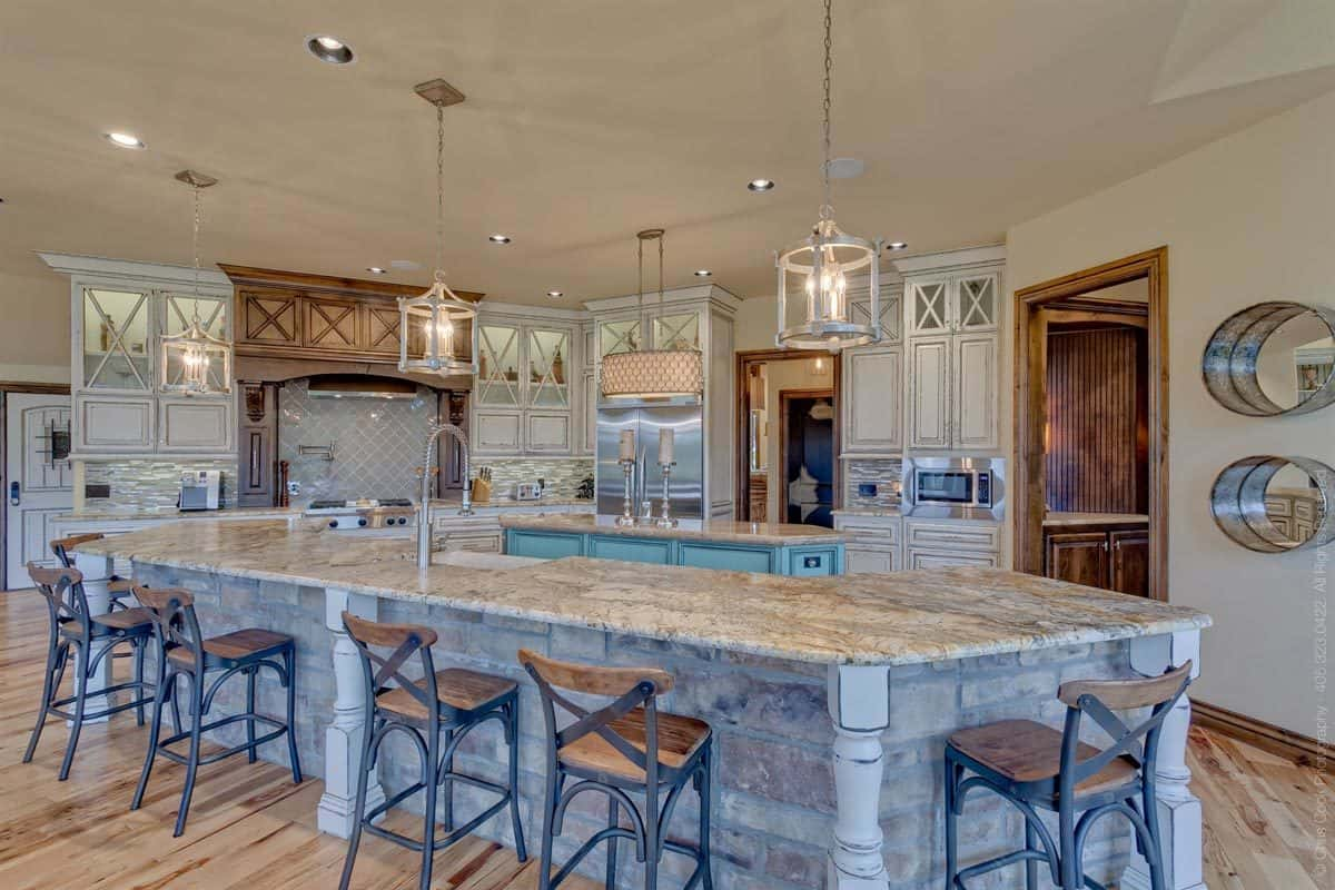 This charming kitchen has two kitchen islands. One has a U-shape that also incorporates the breakfast bar paired with wrought iron stools. The other is a smaller one in the middle of the kitchen.