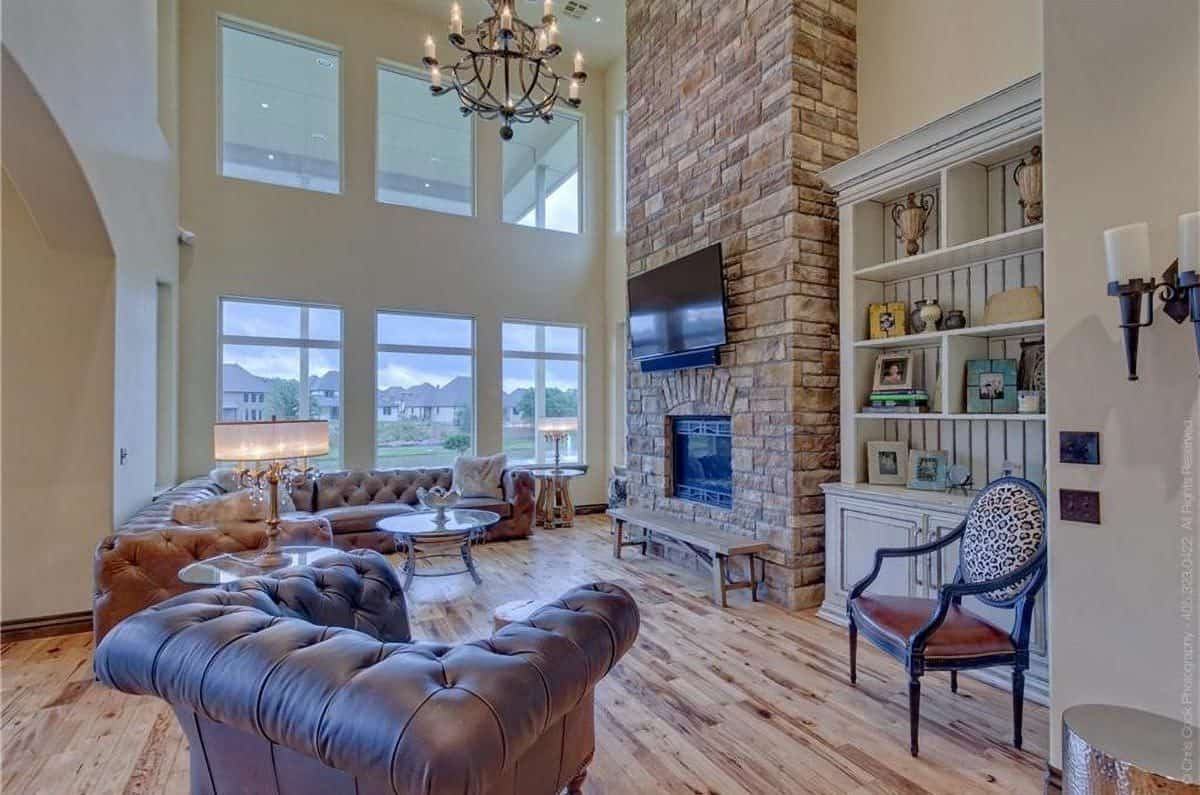 This living room has a tall ceiling complemented by tall windows and a chandelier. This living room is also dominated by the large stone brick structure that houses the fireplace and the TV across from the sectional brown leather sofa and arm chair.