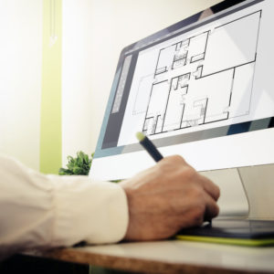Architect at desk designing building on the computer