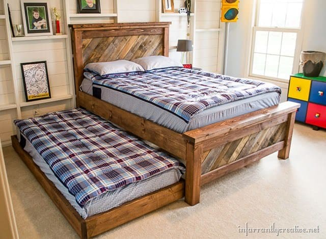 Check this out - this bed is built with a traditional frame style and uses pallet boards for the headboard and end. Includes a trundle bed as well.