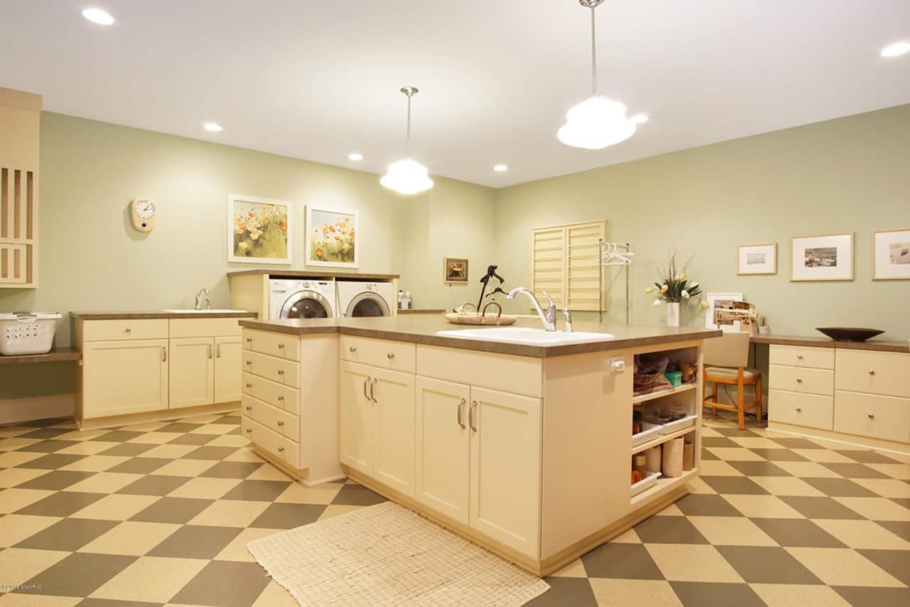 Massive laundry and utility room with island, cabinetry and shelving.