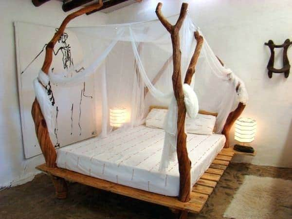 The platform bed is made from pallets.  The 4 posts are small tree trunks which has a thin canopy draped over it.