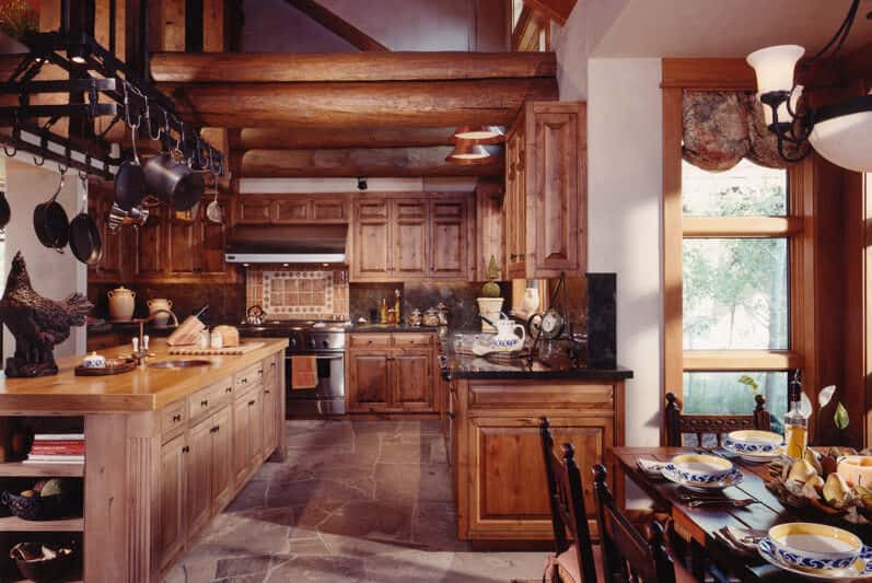 A glamorous kitchen space surrounded by a rustic finished ceiling, cabinetry, bar counters and center island. The flooring adds class to the already stunning kitchen.