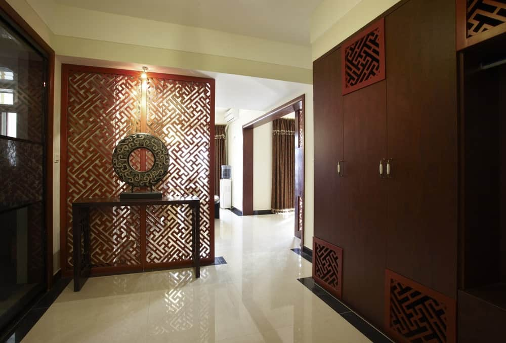 This simple Asian-style foyer has a distinctly Chinese flair to its red panel screen that is filled with patterns. It acts as a room divider between the foyer and the rest of the house. This matches with the designs on the built-in cabinets on the right.