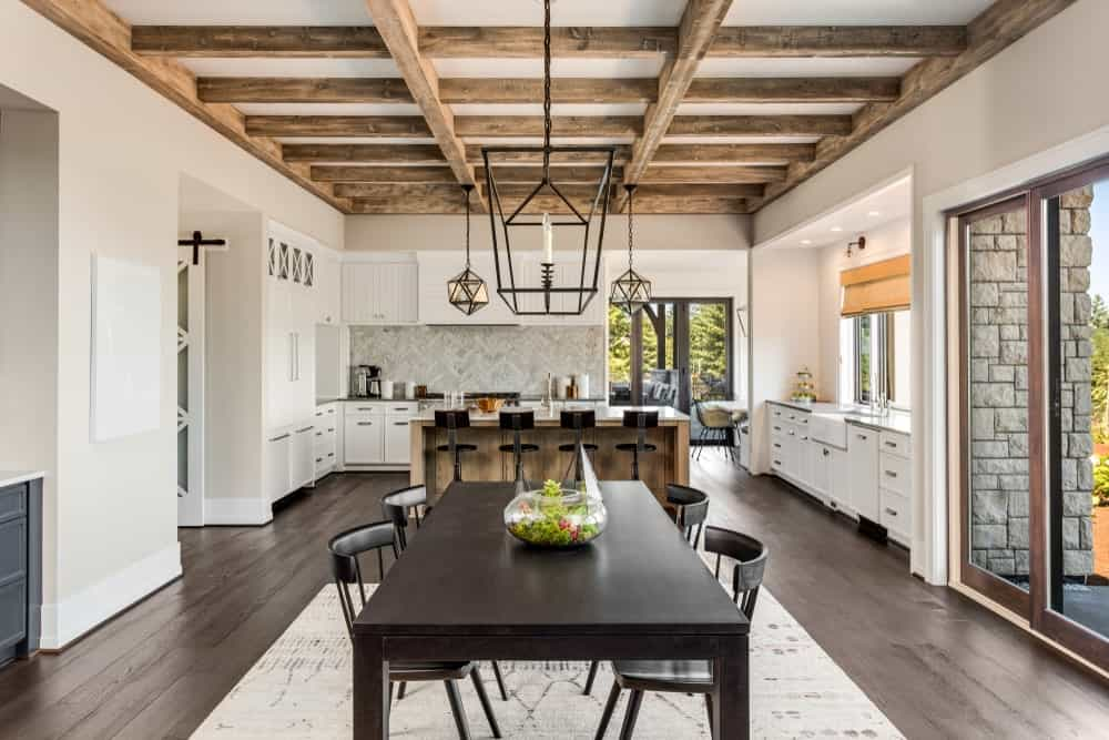 Large kitchen area featuring hardwood floors and a ceiling with rustic beams lighted by a stunning set of ceiling lights. The rustic center island looks very charming as well.