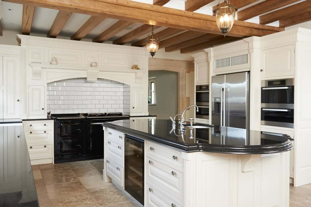 This kitchen features a large center island with a black countertop, set on the classy tiles flooring. The ceiling with beams offers two charming pendant lights.