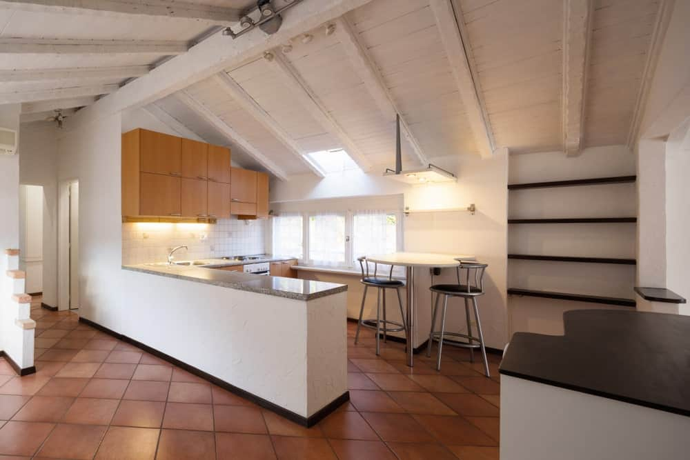 This kitchen features classy tiles flooring and white vaulted ceiling with beams. There's a small breakfast bar too, perfectly placed on the side.