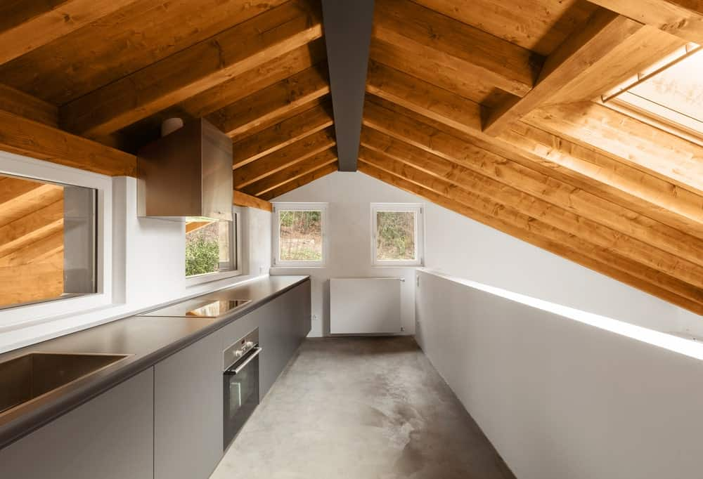This kitchen boasts stylish gray kitchen counter under the vaulted ceiling with exposed beams.