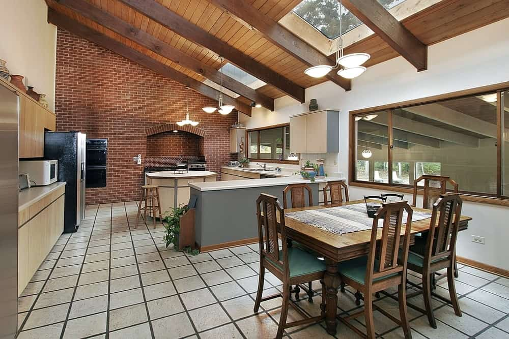 This kitchen features a classy wall and tiles flooring, along with a lovely kitchen counters and center island under the shed ceiling with beams, lighted by gorgeous pendant lights.