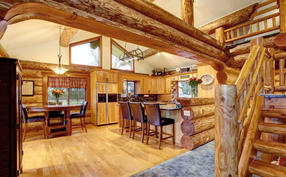 This kitchen features wooden logs all over the place as part of the home's style. The kitchen set matches the hardwood flooring and the exposed beams on the ceiling. This kitchen is very stunning.
