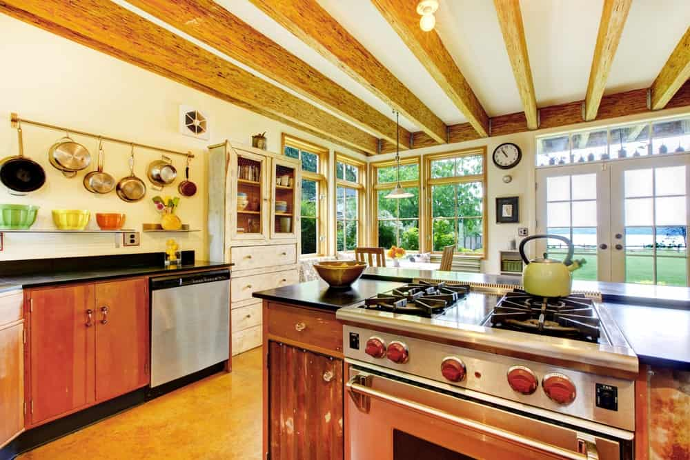 This kitchen features classy kitchen counters with black countertops, along with a ceiling with exposed beams.