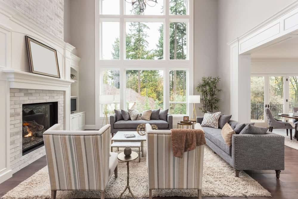 Large living room with gray couches and classy seats set on the white rug. The fireplace keeps the temperature warm. The high ceiling makes the room look stunning.