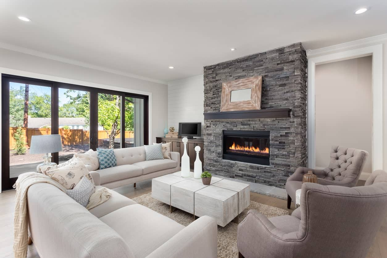 Large living room with a stylish fireplace. The comfortable and classy sofa set is just glamorous in this living room.