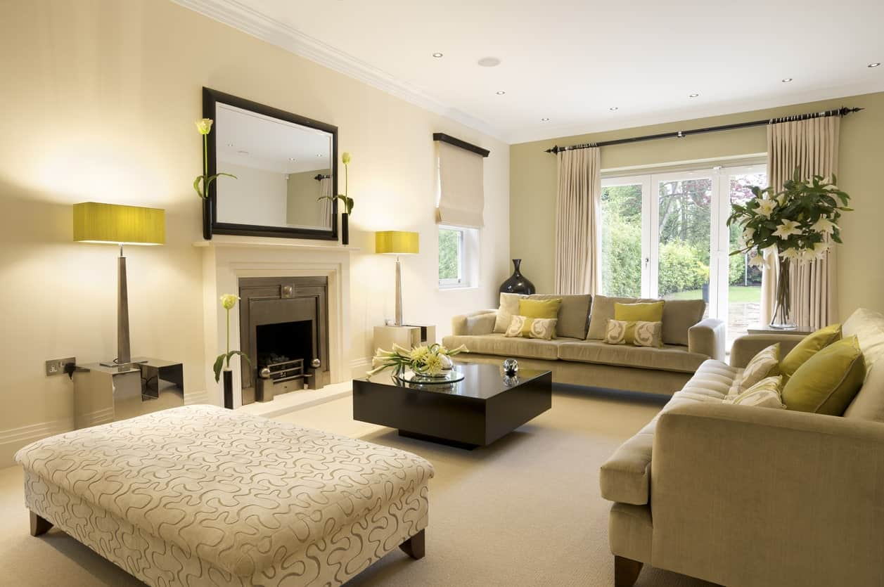 Large and modish living room with stylish seats and center table near the fireplace. The carpet flooring looks smooth together with the beige walls.