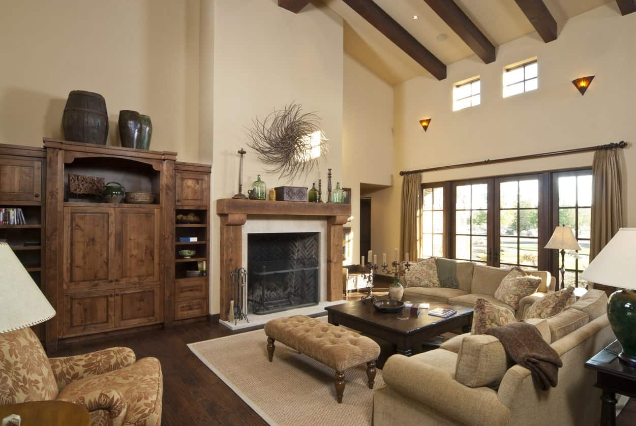 Mediterranean living room with a classy set of the sofa on a rug. The hardwood flooring matches the beams on the ceiling. The beige walls look beautiful when being lighted by the wall lights.