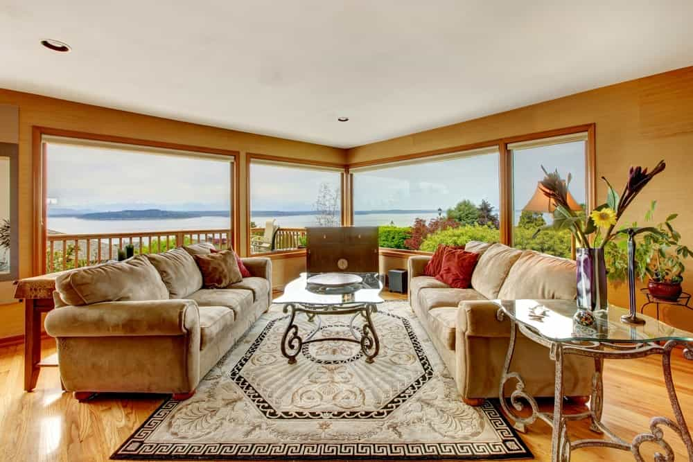 Large and stunning living room with a lovely set of sofa and a stylish rug on a hardwood flooring. The glass mirrors offer a jaw-dropping view of the beautiful nature outside.