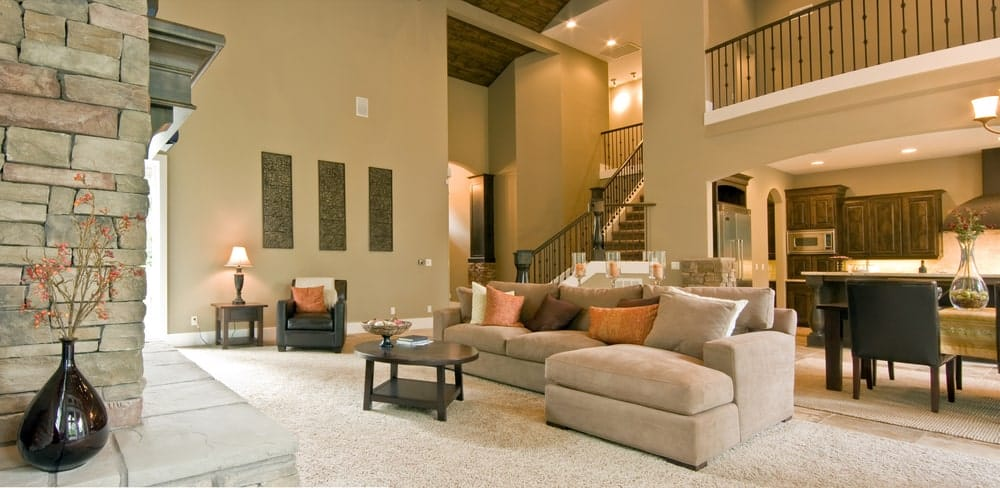 Large living room with white carpet flooring and beige walls matching the gorgeous sofa in front of the fireplace.