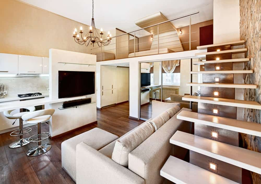 A modern living room with a comfortable couch in front of a TV. The hardwood flooring looks great together with the beige walls that are lighted by a glamorous chandelier.