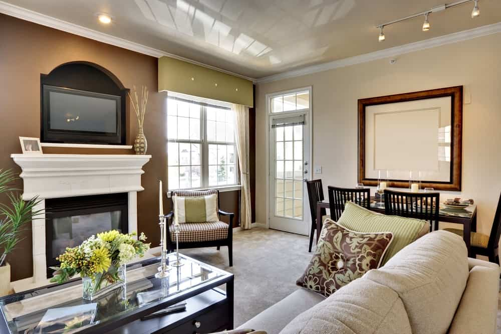 This living room offers a carpet flooring, cozy couch and a glass top center table along with a fireplace.