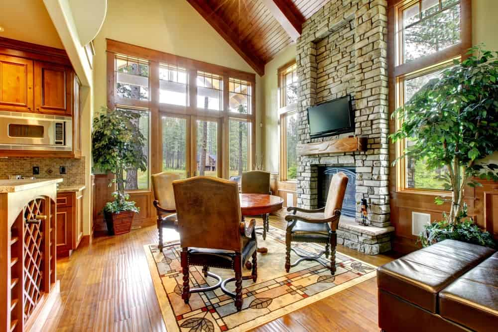 Rustic living room with classy rug and a small round table set near the fireplace.