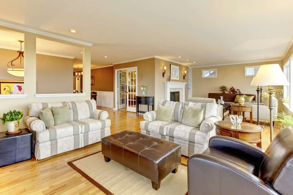 Large living room with stylish seats and romantic warm white lights all over the place.