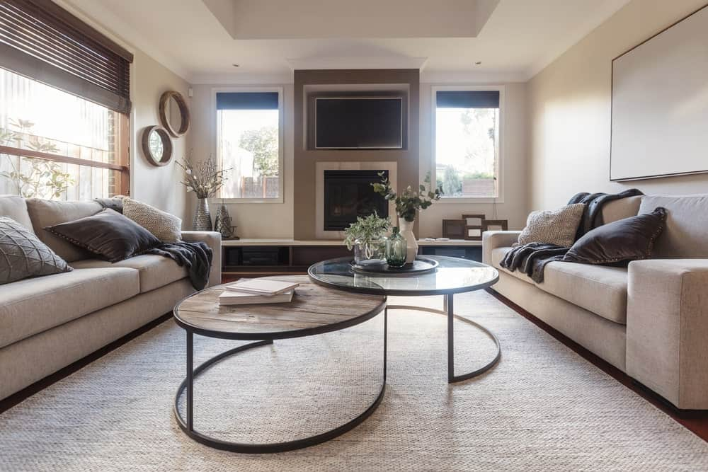 Modish living room with a matching sofa set with a stylish set of center tables. The beige walls look absolutely glamorous.