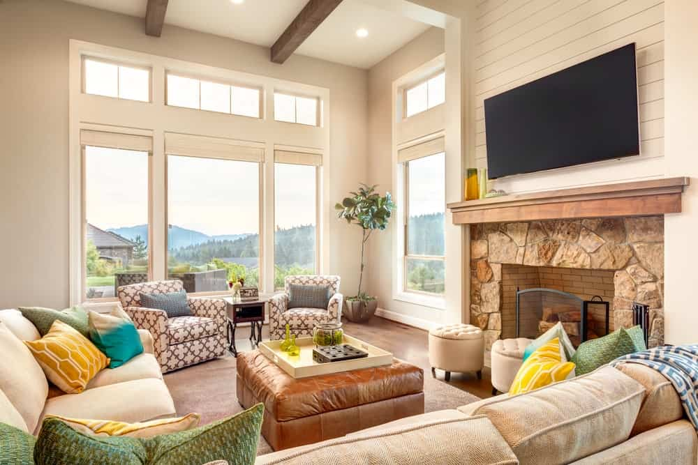 This living room features a high ceiling with glass windows overlooking the stunning outdoor view. The seats are all comfortable and classy. There's a fireplace with a wide screen TV on top.
